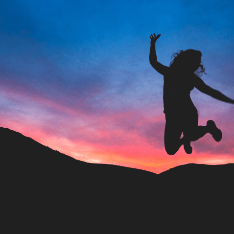 silhouette of person jumping at sunset